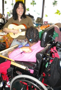 women with guitar plays for child in wheelchair
